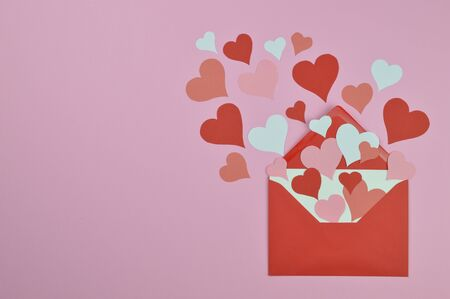 white blank letter in open red envelope with lots of red and white paper hearts Imagens