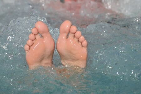 Female bare feet out of bubbling water in a hot tub outdoors in summertime in vacation