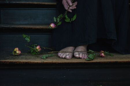 dead roses and woman in black linen dress as a symbol for divorce or a weeping widow