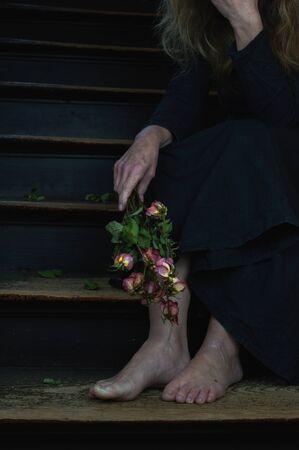 dode rozen en vrouw in zwarte linnen jurk als symbool voor echtscheiding of een huilende weduwe Stockfoto