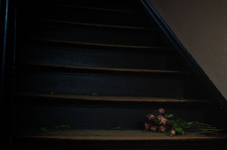 bouquet of dead roses on dark stairs as a symbol of grief and death