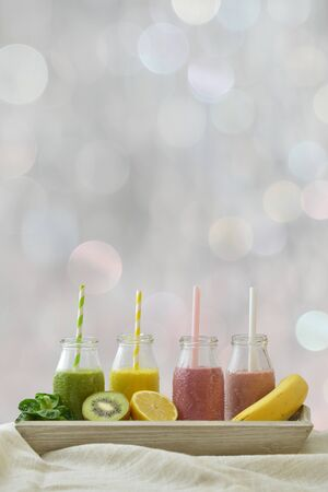 four colorful fruit smoothies in a row with fresh fruits in front of a neutral bokeh background with copy space above for a healthy lifestyle