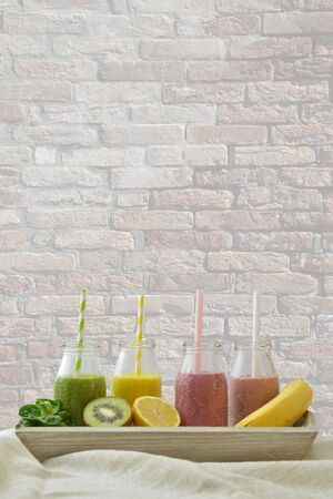 four colorful fruit smoothies in a row with fresh fruits in front of a brick wall with copy space above for a healthy lifestyle Imagens