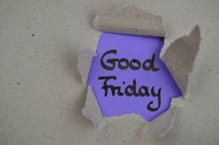 the words good friday on purple paper shown under torn open brown paper