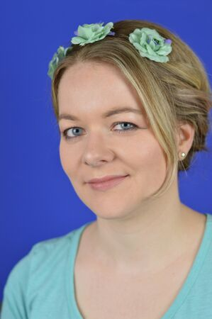 portrait of a pretty blond caucasian woman with hair and cyan flowers on a circlet smiling in front of blue background
