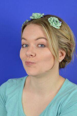 circlet ruminating in front of blue background. Portrait of a young blond caucasian woman with updo hair and cyan flowers on a circlet Imagens