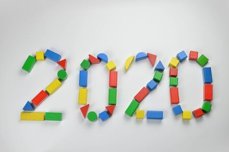 Number of the year 2020 written with colorful yellow, green, red and blue toy wooden blocks