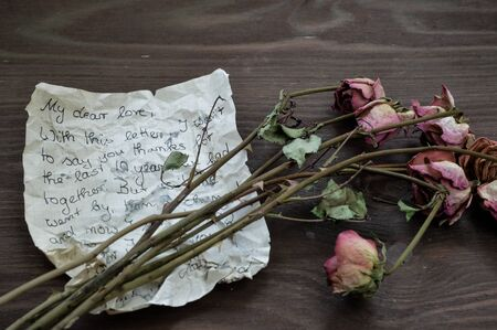 old rumpled farewell letter with withered roses on brown wooden table as keepsake for a long lost love 스톡 콘텐츠