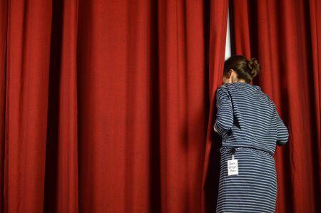 Vrouw met een backstage die uitkijkt over de rode gordijnen op een podium Stockfoto