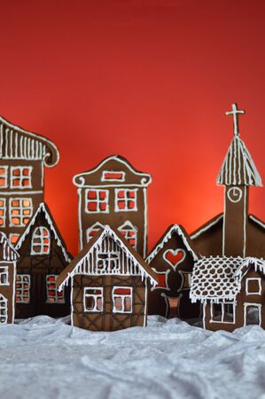 Home made traditional sweet delicious baked gingerbread village in front of red background on white snowlike velvet as christmas decoration for the family