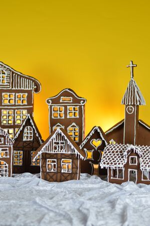 Home made sweet delicious baked gingerbread village with white background on white snowlike velvet Imagens