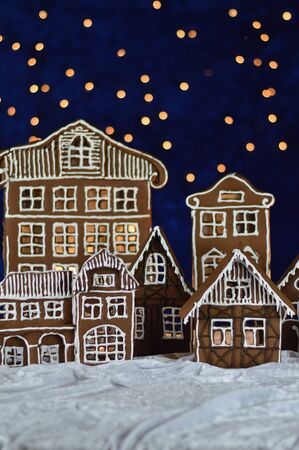 Home made gingerbread town with bokeh sky out of blue velvet and christmas lights Imagens