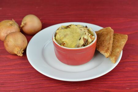 Onion soup with bread and cheese next to a traditional autumnal food Imagens