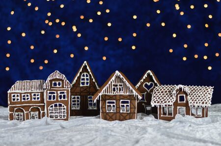 Home made gingerbread town with bokeh sky out of blue velvet and christmas lights
