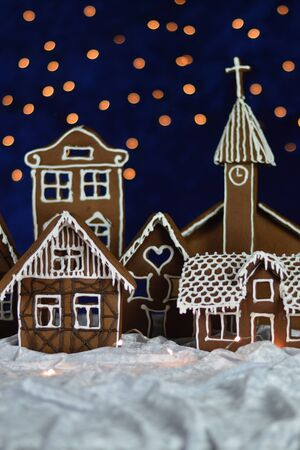 Home made gingerbread town with church and bokeh sky out of blue velvet and christmas lights