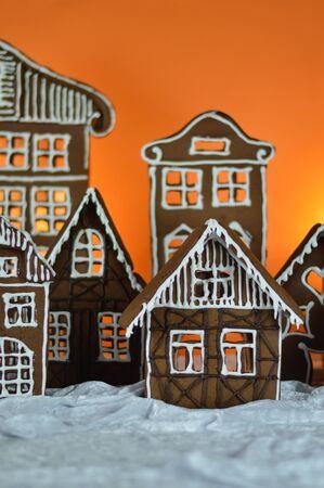 Gingerbread village in front of orange background on white snowlike velvet as christmas decoration for the family