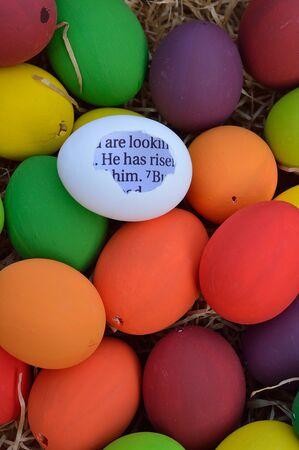 Bright white egg with broken shell and the bible passage HE HAS RISEN inside between many multicolored Easter eggs