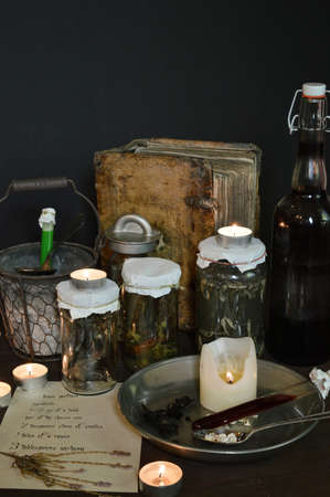 eerie witches' kitchen with lot of ingredients for a love potion and ancient gruesome jars dark with only candlelight for Halloween
