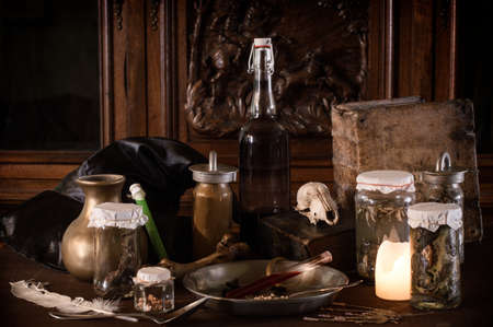 eerie witches' kitchen with lot of ingredients for a potion and ancient gruesome jars dark with only candlelight for Halloween