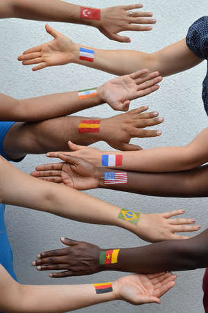 International brothers and sisters, men and woman from different nations with flags painted on their arms stretching out their hands to each other in peace