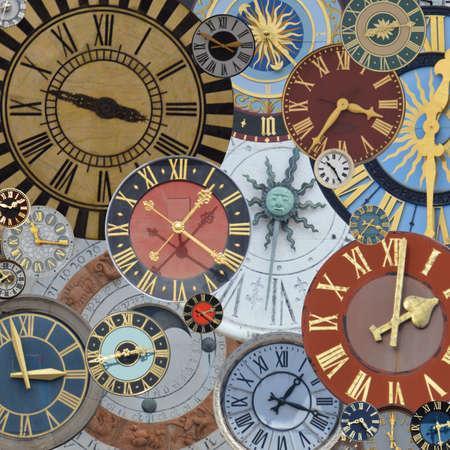 multicolored collection of ancient church tower clocks on a pile in different sizes and forms with roman numbers Imagens - 164035188