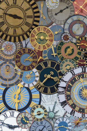 multicolored collection of ancient church tower clocks on a pile in different sizes and forms with roman numbers