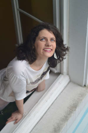 A woman looking delighted out of the window Imagens
