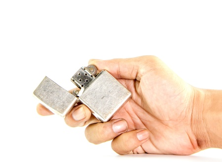 Vintage silver gasoline lighter in man hand isolated on white background photo