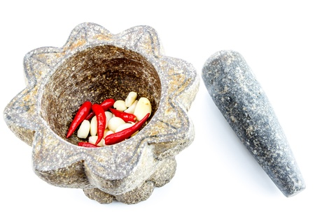 garlic and red chili pepper in stone mortar on white background photo