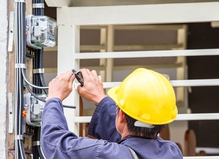Electrician connects a Power meter  photo