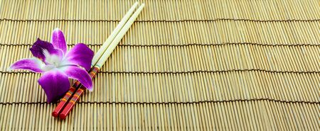 chopsticks on bamboo mat with orchid photo
