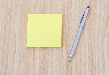 yellow notepad: Blank yellow notepad with pen on office wooden table Stock Photo