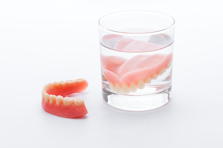 surrogate: Full Denture in glass of water on white background