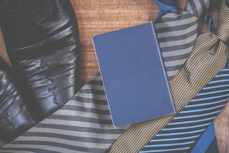 notecard: Necktie and shoes,passport on grunge wood background