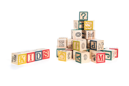 and spelling: photo of a alphabet blocks spelling kids isolate on white background Stock Photo