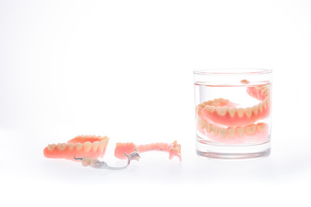 surrogate: Dentures in glass of water on white background