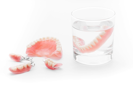 surrogate: Set of Denture in glass of water on white background