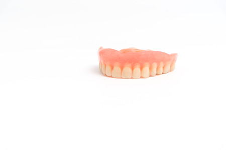 fake smile: upper dentures on white background Stock Photo