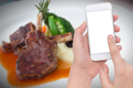 Female  hand holding a phone on Blur lamb steaks dinner background Stock Photo