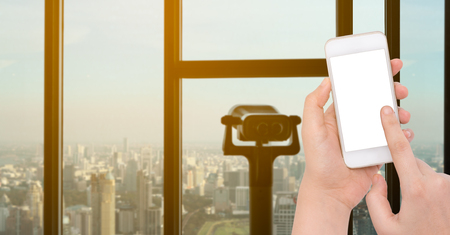 Female  hand holding a phone on blurry binoculars and city view with sunlight background Stock Photo