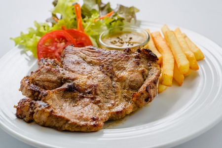 Pork steak with french fries and salad ready to serve. photo