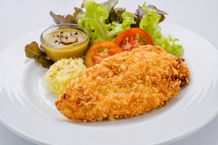 Breaded chicken with mashed potatoes and salad.