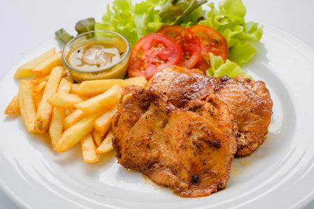 Chicken steak served with french fries and salads to vegetables. photo