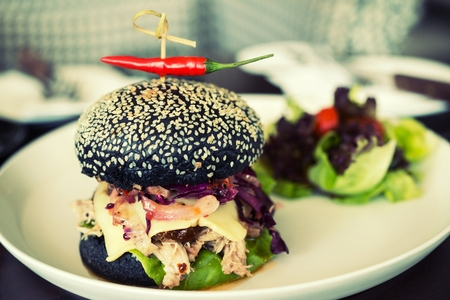 Pork hamburger made from bread Breeze Yacht mixing bamboo charcoal black. Served with salad and fried potato discs.