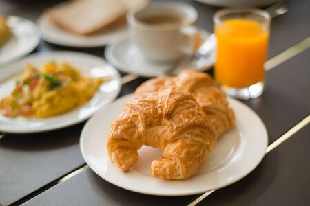 Croissant Breakfast served with black coffee and a breakfast menu, such as orange juice, jam, eggs, filling it. photo