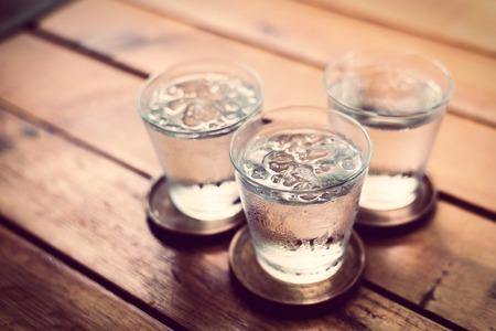 vasos de agua: Beber agua fr�a en un per�odo de tres de vidrio colocado sobre la mesa de madera.