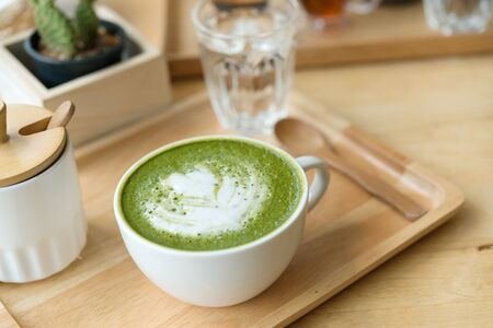 Hot green tea set on a wooden table in a coffeshop Stock Photo