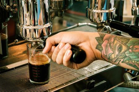 Coffee machine making coffee holded by tattooed barista arm Stock Photo