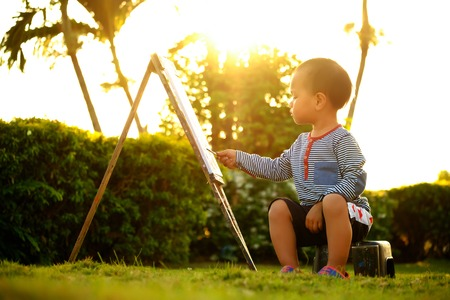 easel: child  painting color drawing at public park is sunset Stock Photo