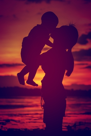 Silhouettes mother carries her son ,is background beautiful sunset on the lake.